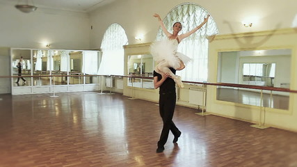 Couple ballet dancing, young man carrying ballerina on shoulder