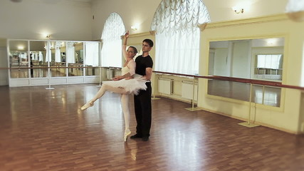 Man and woman rehearse ballet moves, take break from dancing