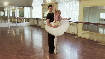Male and female ballet dancers exercising in gym, slow motion