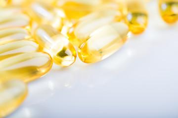shiny yellow vitamin e fish oil capsule on white background