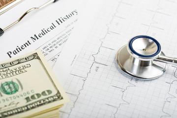 stethoscope over ecg graph and 100 dollar bills