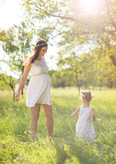 Pregnant mother with her little daughter in nature