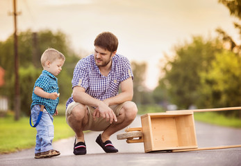 Father and son on road with wheelbarrow