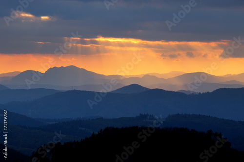 Sunset over color mountain silhouette. - 72129787