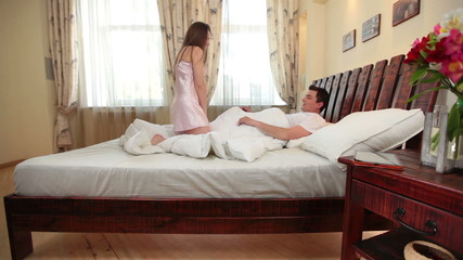 Young attractive couple holding hands, kissing, hugging in bed