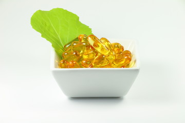 Fish oil capsules with vegetable leaf in cup on white background