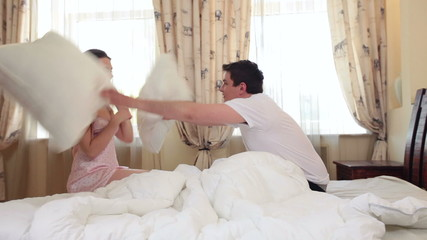 Cute couple play pillow fight then start kissing and undressing
