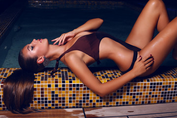 beautiful woman in bikini posing in night swimming pool