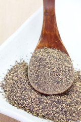 Close - up Black pepper powder in wooden spoon