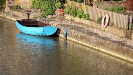 Blue rowing boat floating on a river.