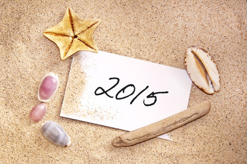 2015, written on a note in the sand with seashells