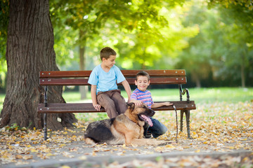 children in the park with a German Shepherd