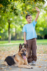 smiling child with a German Shepherd Dog in the park