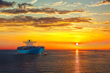 Container ship on sea road during sunrise.