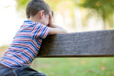 orphan, unhappy boy sitting on a park bench and crying poster