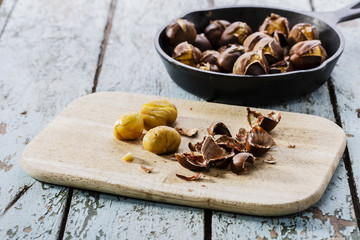 roasted chestnuts in the pan on a wooden surface