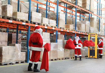 Santa claus looking for gifts in storehouse full of presents