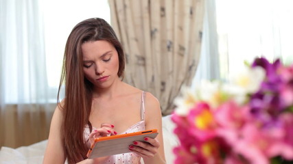 Pretty young woman in lingerie checking tablet pc in bedroom