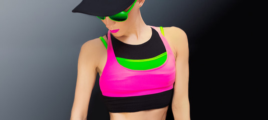 fitness lady in bright trendy sportswear on a black background