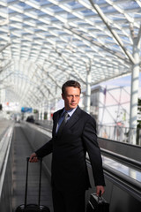 business man travel with bag and trolley on escalators