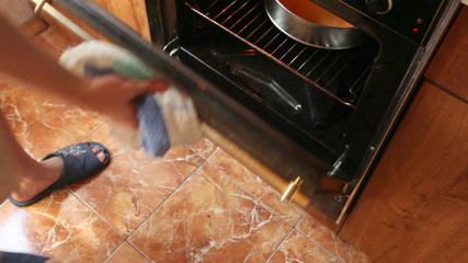 man pulls out of electric oven hot form with azyme cake