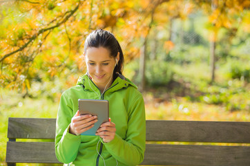 Young woman with tablet in autumn park.
