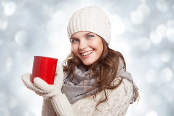 Beautiful smiling woman with a cup of coffee on the winter backg