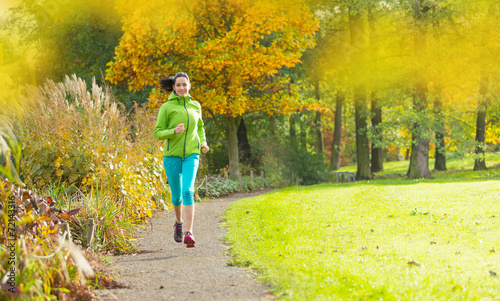 canvas print picture Young brunette woman running in park.