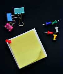 Note pad, Pushpin and Binder clip on black background