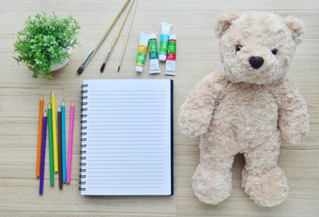 Blank paper, color paint and bear doll on the wood table - Top v