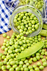 Green peas in glass jar on board