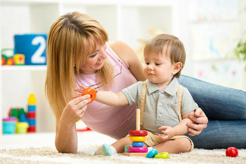 cute mother and child boy play together indoor at home