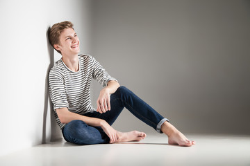 casual young man posing on floor smiling over gray