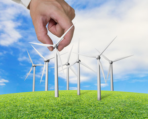 hand holding wind turbines on grass