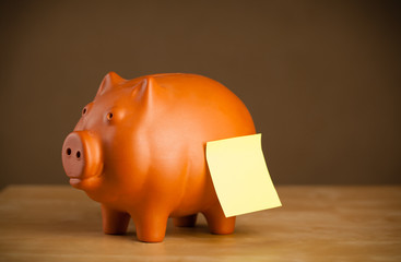 Empty post-it note sticked on piggy bank