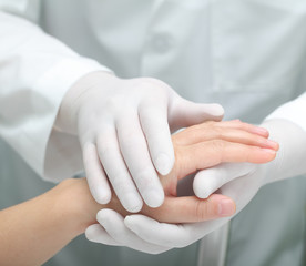 Doctor comforting a sick woman. Hands in warm touch.