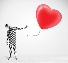 Cute guy in morpsuit body suit looking at a balloon shaped heart
