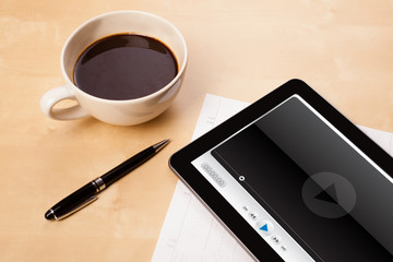 Tablet pc showing media player on screen with a cup of coffee on