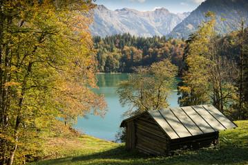 Idylische Hütte im Herbst am See mit Bergen