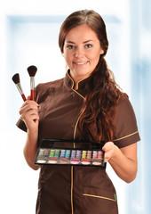 Professional beautician holding brushes