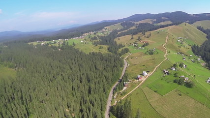 Flight over  hill in mountains with wood and village. Aerial
