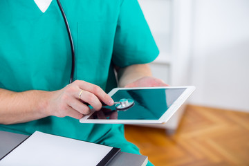 The doctor puts a stethoscope on a digital tablet