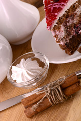 Piece of chocolate cake and white meringue on wooden background