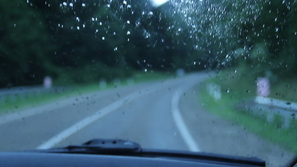 Driving in rain, drops on windshield, poor visibility, danger