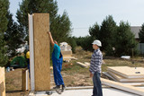 Builders erecting insulated wall panels poster