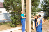 Team of builders erecting wall panels poster