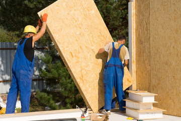 Construction workers positioning wall panels