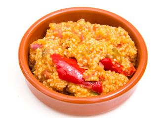 Couscous with vegetables on a bowl over white background