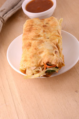 Burrito on white plate with sauce on wooden background