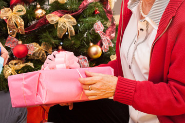 Grandpa putting present under Christmas tree